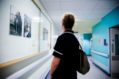 Nurse looks at one of the photos as she passes