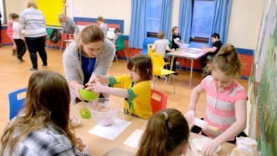 Children engaging in a craft activity with a support working at a young carers group in Norwich.